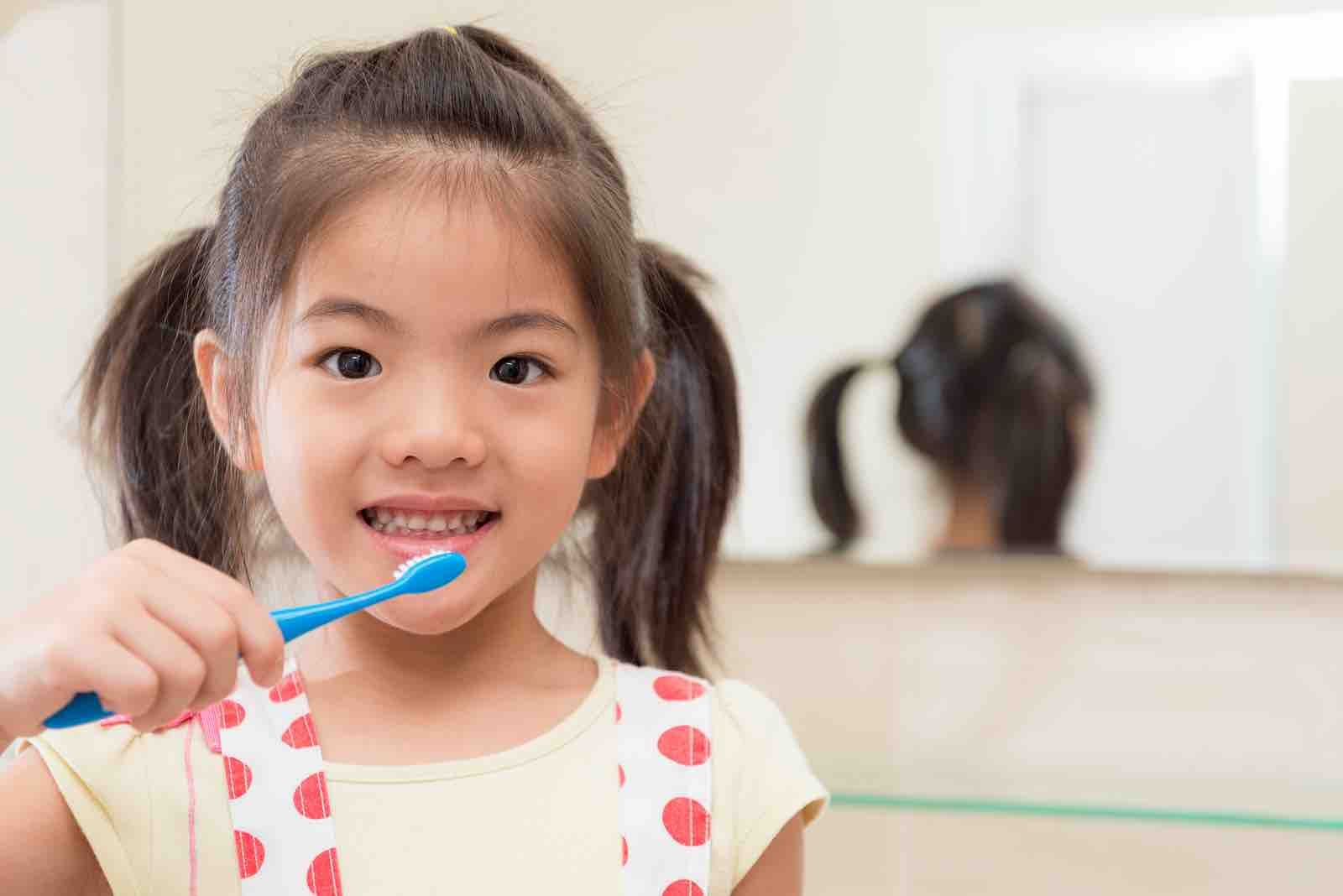 Bellaire pediatric dentist with girl brushing teeth.